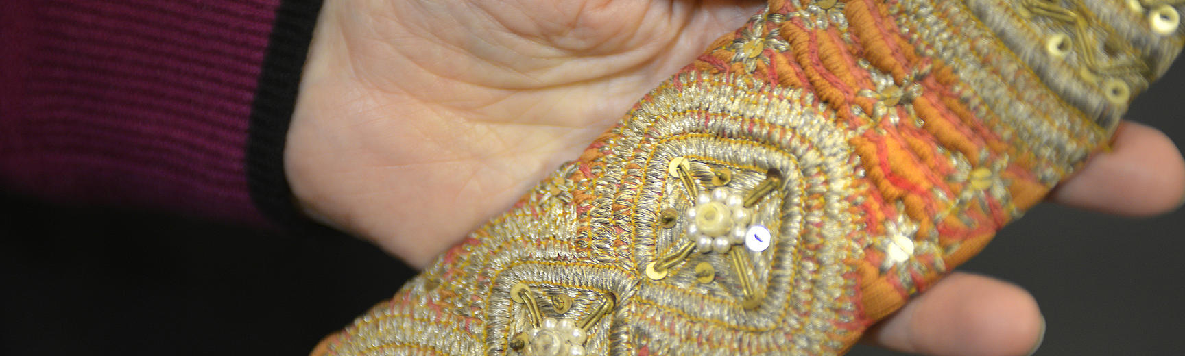 Hand holding a textile richly decorated with metallic threads, beads and sequins