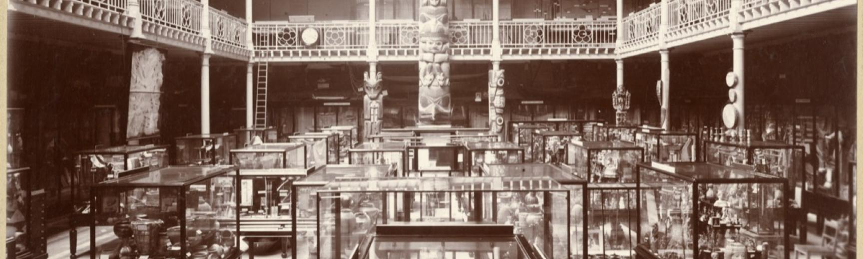 Interior view of the Pitt Rivers Museum, looking towards the east end of the Court, showing the Haida totem pole. Photograph by Alfred Robinson. Oxford, England. Circa 1901. (Copyright Pitt Rivers Museum, University of Oxford. Accession Number: 1998.267.2