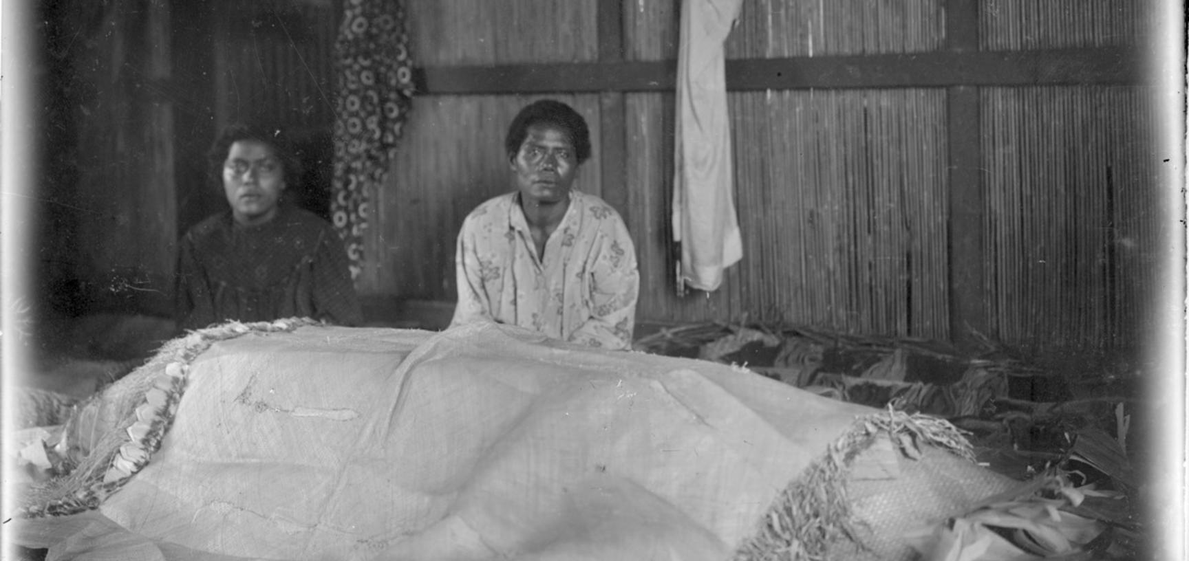 Women with coffin of a child, covered in funerary wrappings, Lakeba, Lau Islands, Fiji, 1909-14.