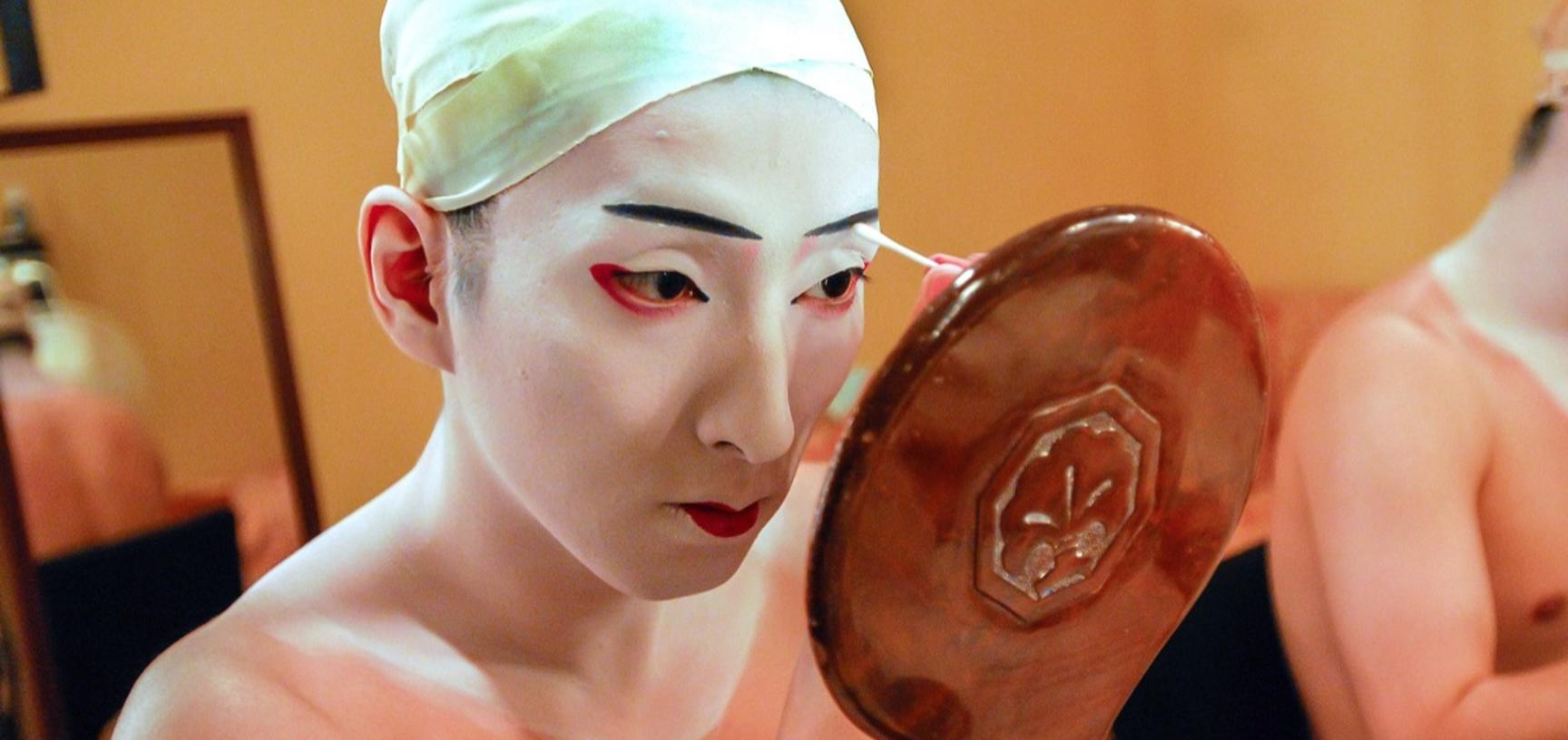 An actor applies heavy make-up to their face while looking in a hand-held wooden mirror.