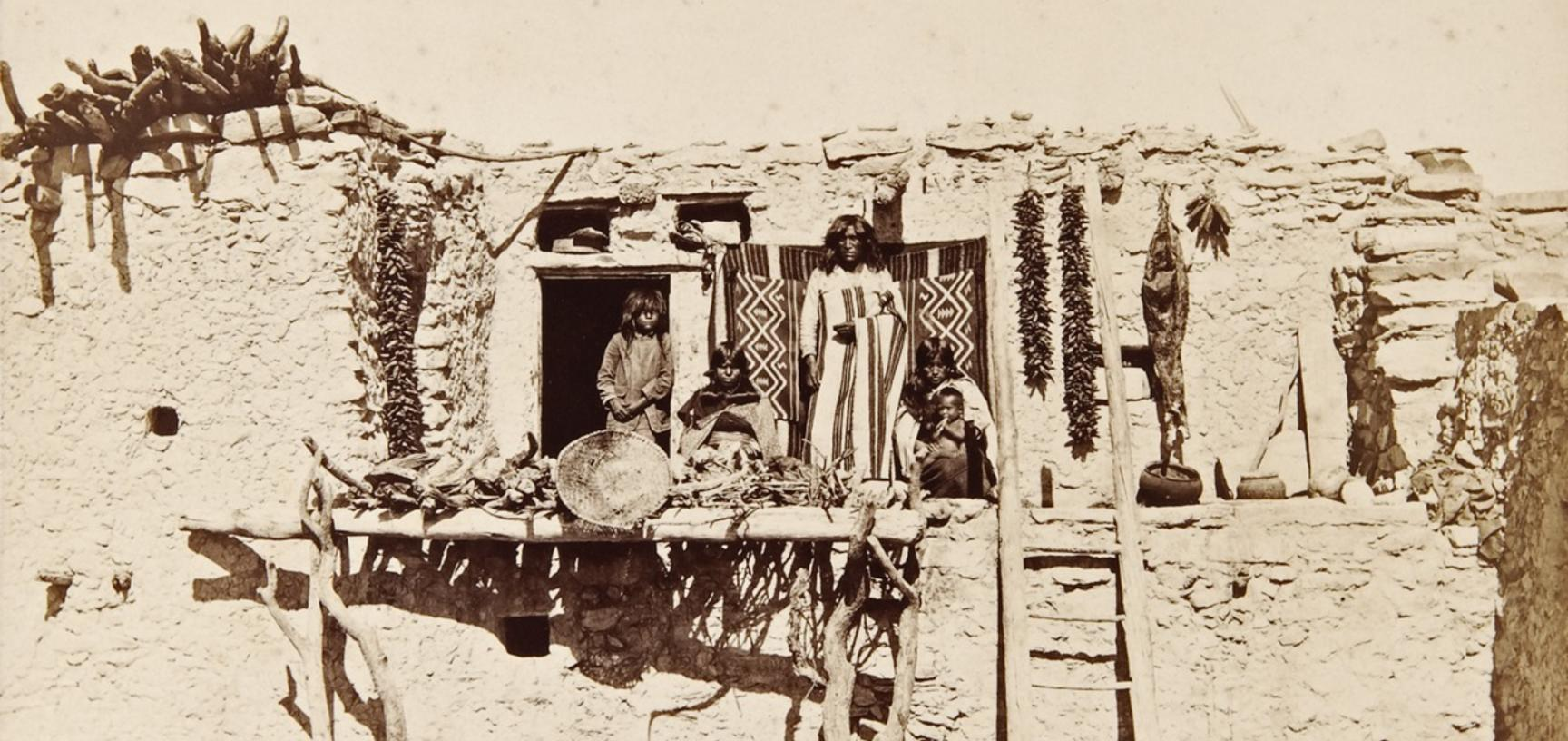 Totci and his family, gathered on a wooden platform in front of their house, with a blanket hanging and crops drying on a wall behind them.