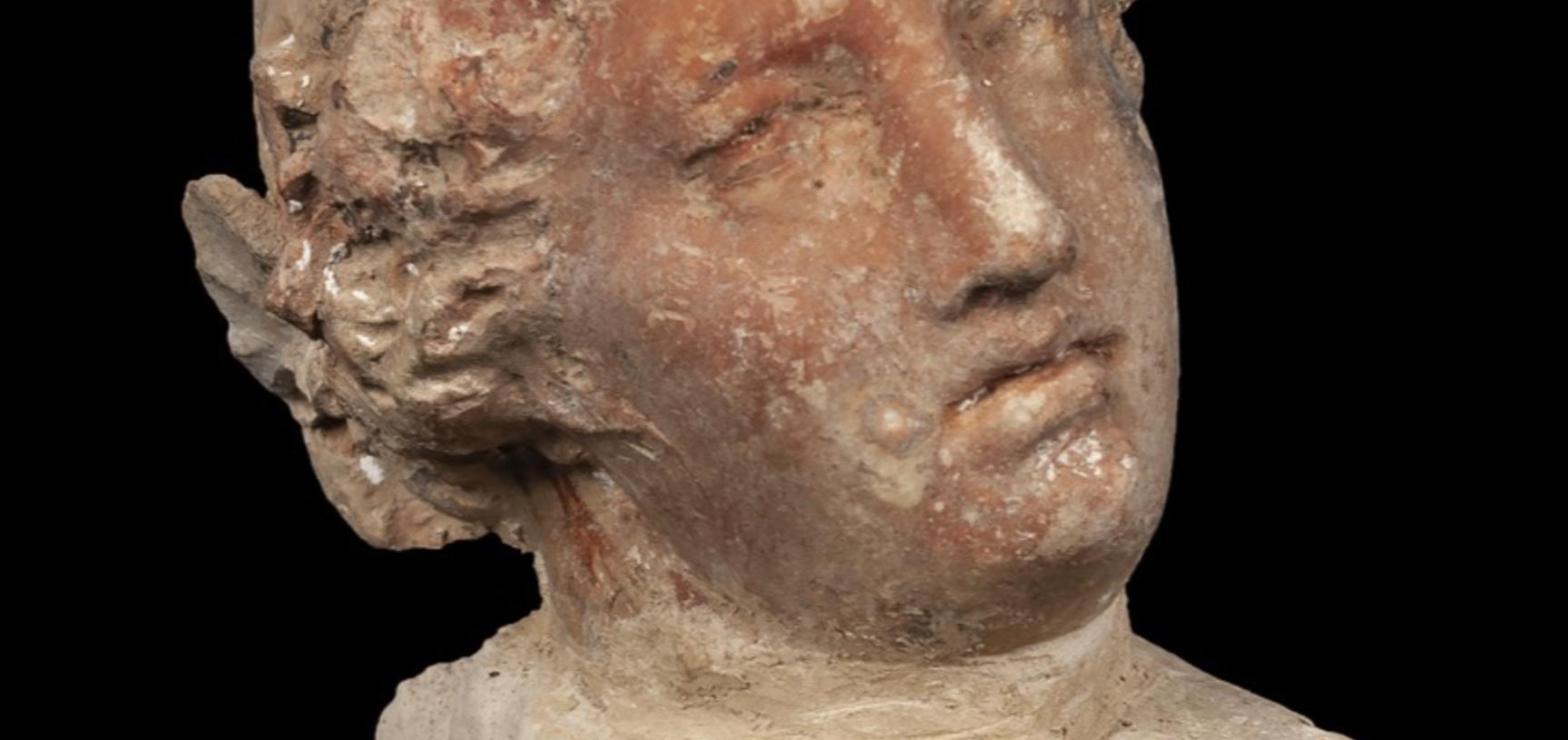 Very small statue of a head with Grecian-style hair.