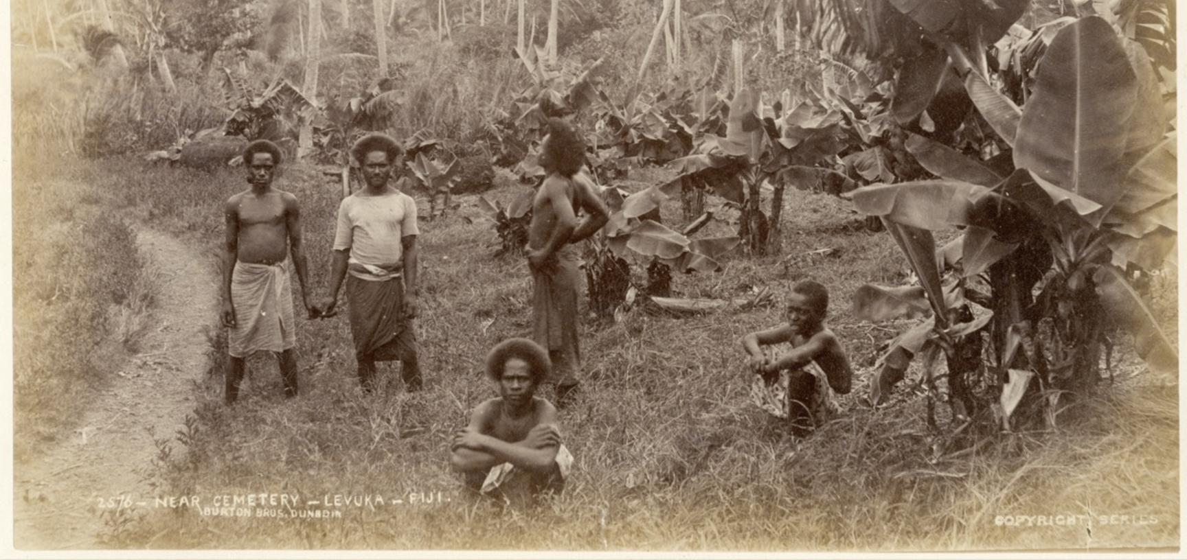 Fijian men near the cemetery at Levuka. Photograph by Alfred Burton for the Burton Brothers studio (Dunedin). Levuka, Ovalau, Fiji. 14 July 1884. (Copyright Pitt Rivers Museum, University of Oxford. Accession Number: 1998.238.10)