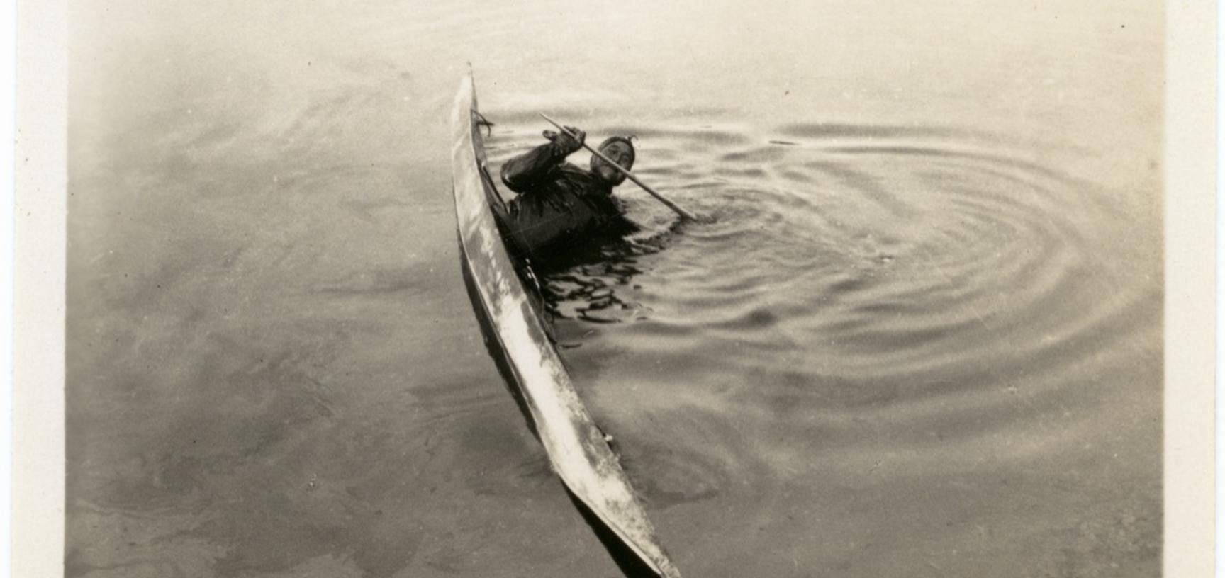 Photograph depicting one of the stages of a 'kayak roll', an exercise to enable kayakers to learn how to right themselves quickly if capsized in freezing waters. Photographer unknown. Greenland. 1930–1931.