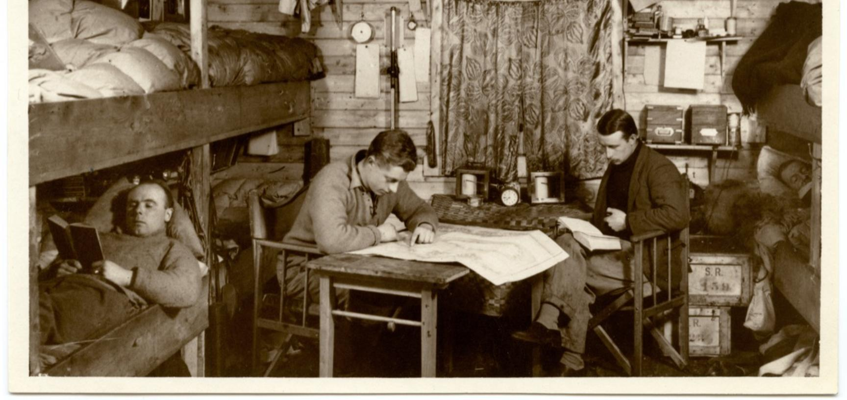 Members of the expedition posed and looking studious in their base hut.