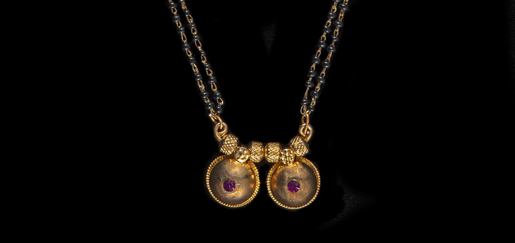 Long gold chain necklace with pendant in the form of two gold breasts