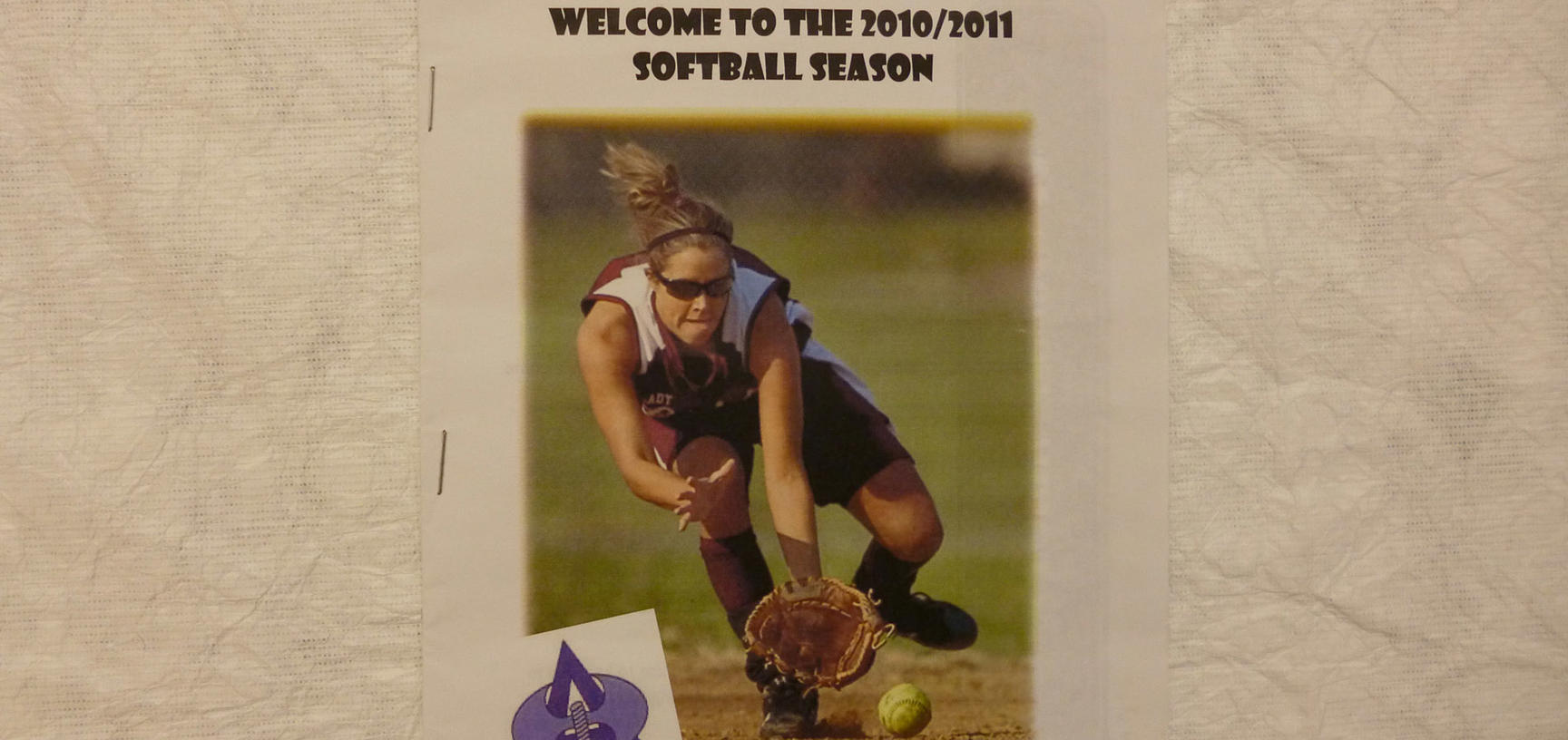 White poster with image of woman playing softball, black text and purple Amazons team logo.