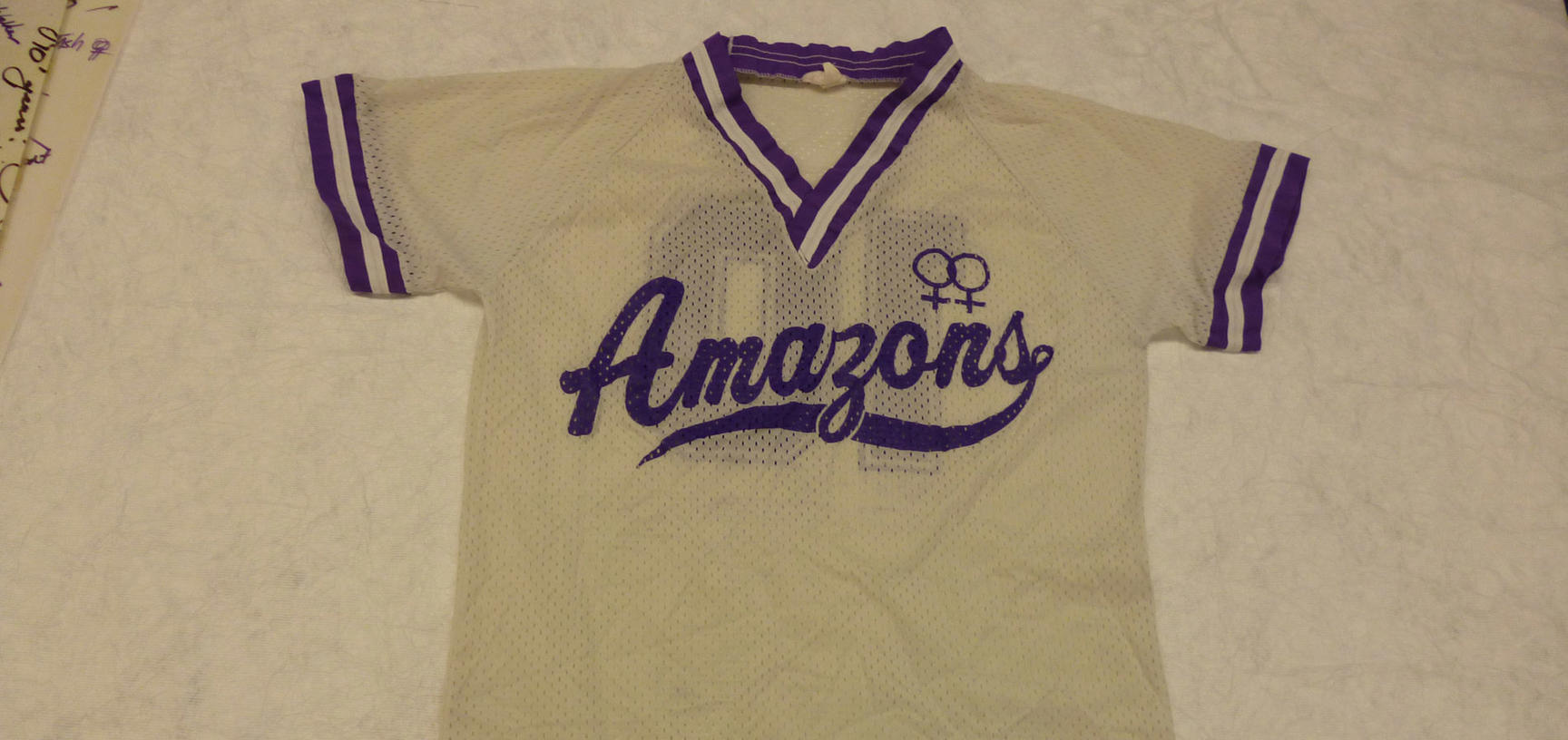 Cream sports shirt with purple Amazons team logo across the front.