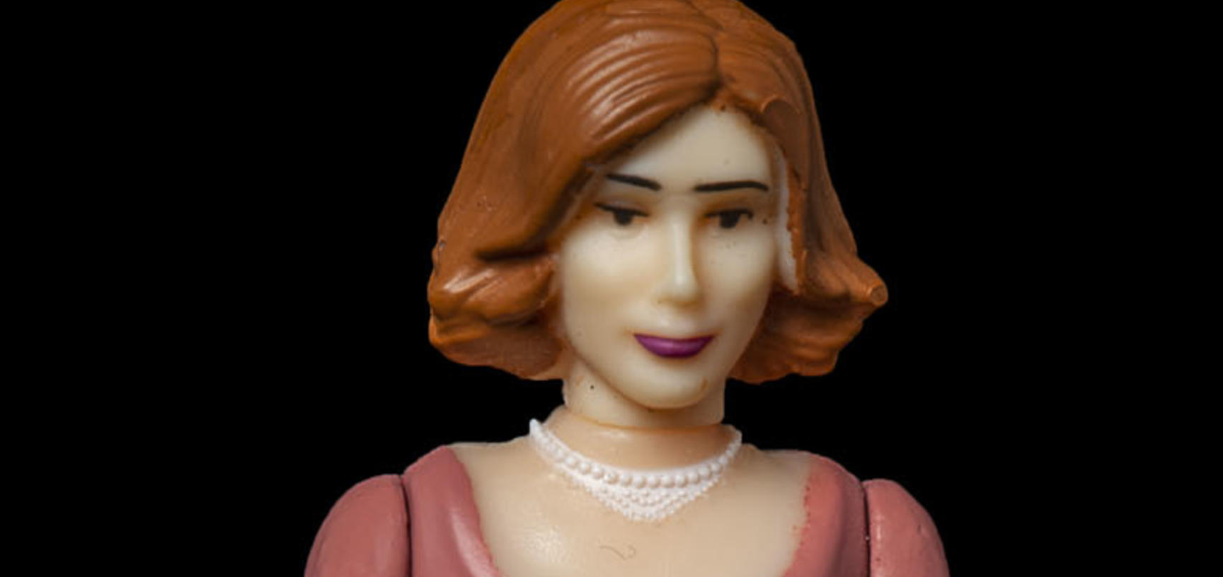 Plastic model of a woman with auburn hair, dark trousers and pink jumper.