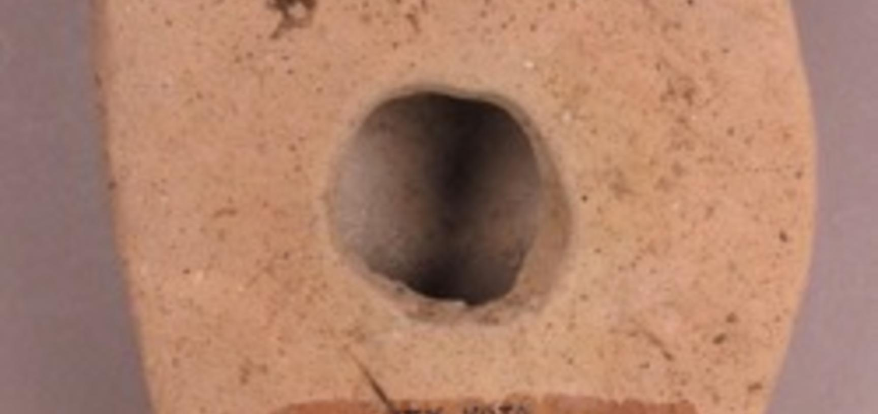 The flat back of a terracotta model, with a hole in the centre and hand-written text.