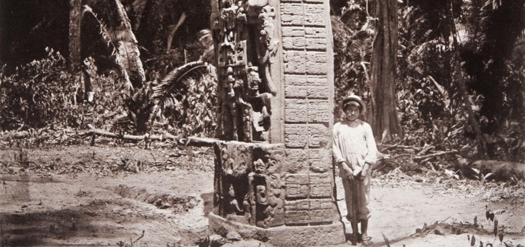 Stela D (Monument 4), west side, dated AD 766. Maudslay has included in the photograph one of his local assistants, or mozos, to show the huge size of the monolith, nearly six metres in height. The sculpture is made of red sandstone, a stone not available