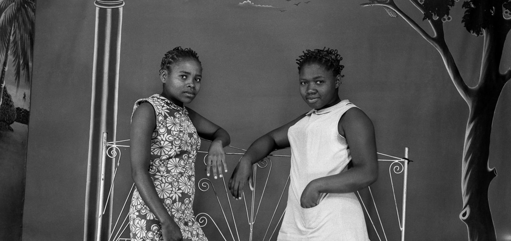 Young women leaning on an ornamental iron grille in front of a painted studio backdrop. Photograph by Jacques Touselle. Mbouda, Cameroon. Early 1970s.