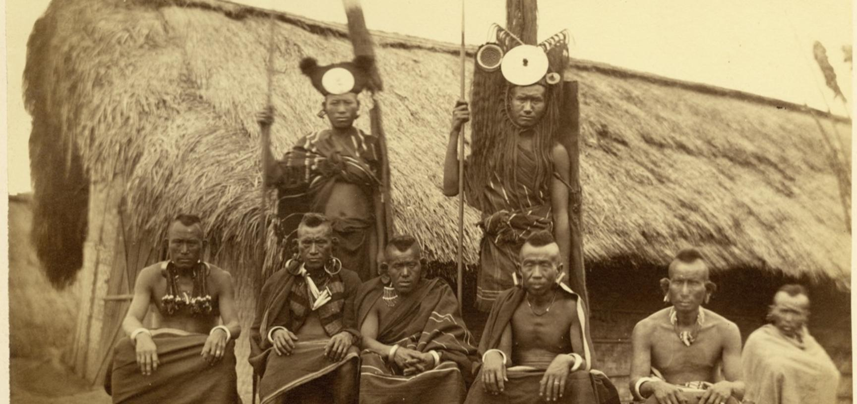 'Tangkhul Nagas' (handwritten caption). Group portrait of Tangkhul Naga men, standing and sitting, pictured in front of a building. Photographer unknown. Naga Hills District of Assam (now in Manipur), India. 1873–1874. (Copyright Pitt Rivers Museum, Unive