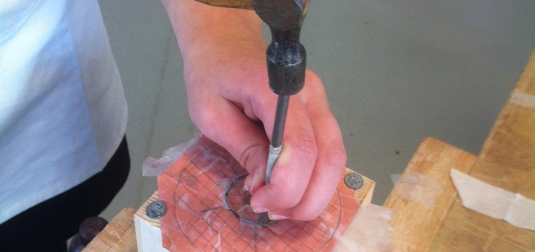 hand engraving a block of wood