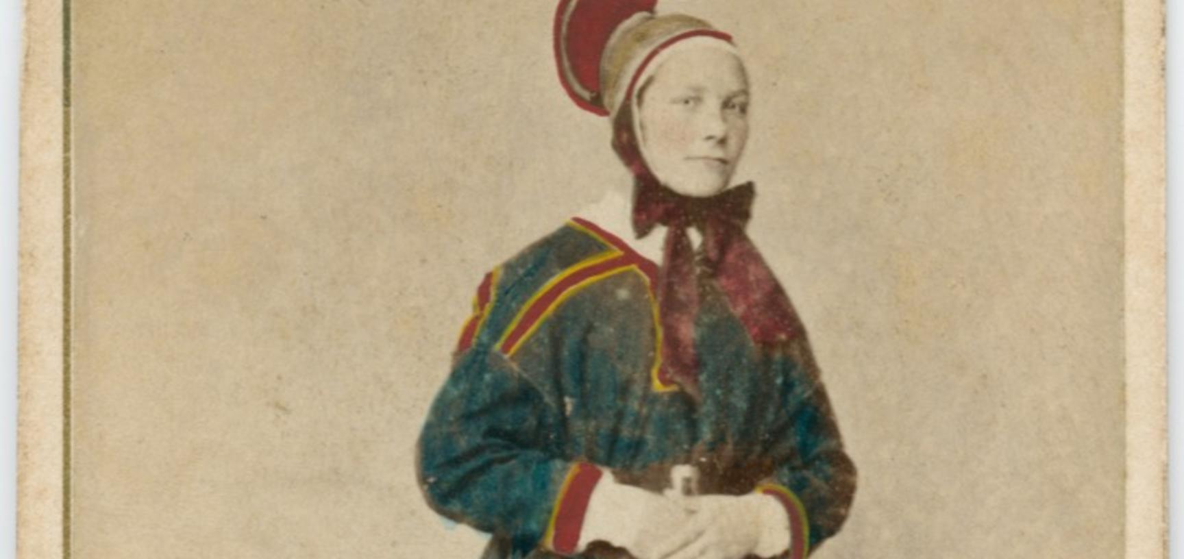 Hand-coloured studio portrait of a Saami woman, identified as a wife (or married woman), standing, wearing a distinctive hat, described on the printed caption as being from Karasjok in Finnmark, Norway. Photograph by the Marcus Selmer studio. Bergen, Norw