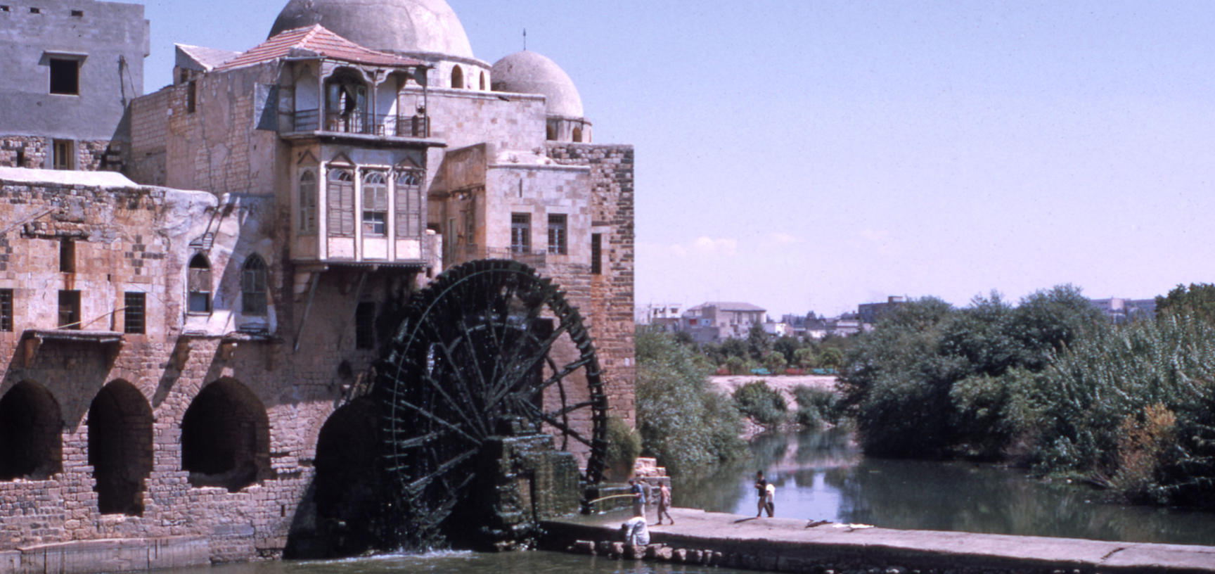 A waterwheel attached to a building rotates over a river.