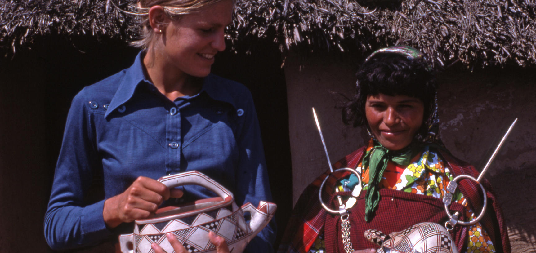 Two women holding pottery items