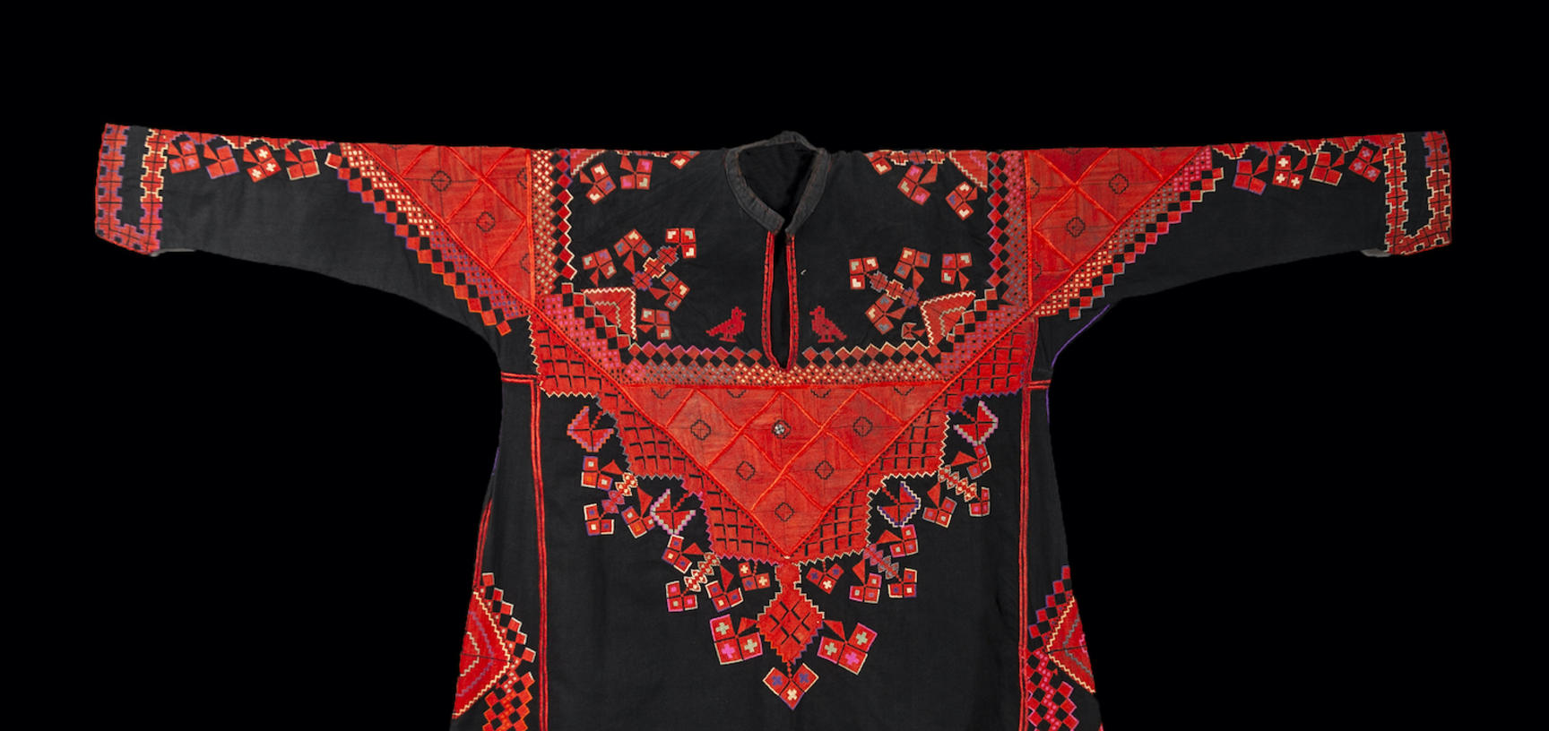 A dark long sleeve dress decorated with red embroidery.