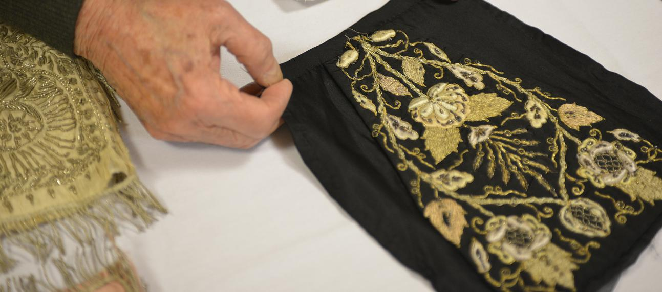 Hands holding a piece of black textile with golden embroidery