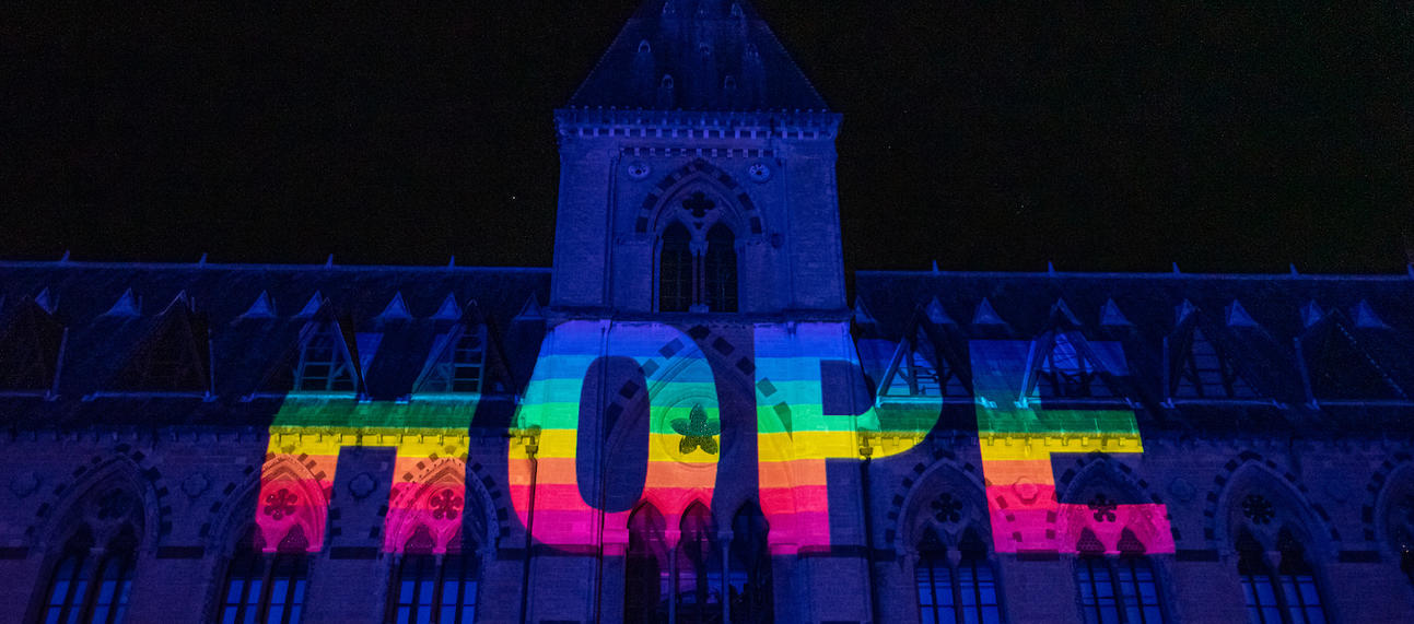 Rainbow letters spelling Hope projected onto dark front of Museum of Natural History