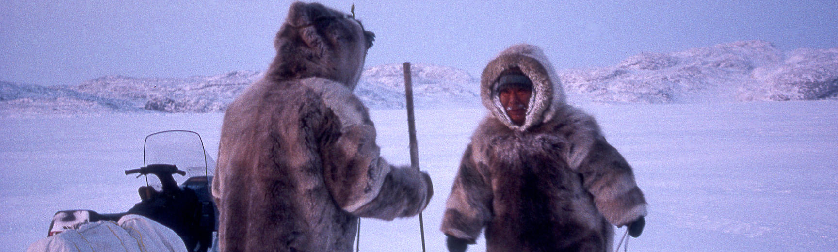 Two Inuit men wearing thick fur coats with hoods up look down into a hole in the ice.