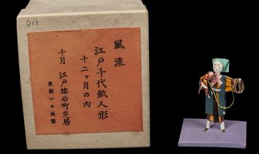 Paper figure of a man holding a monkey on a lead next to a brown and orange box with Japanese characters on the front.