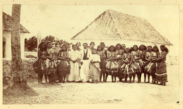 Group of men and women, the Samoan missionary and his wife and daughter standing outside the Mission Station house at Nukufetau
