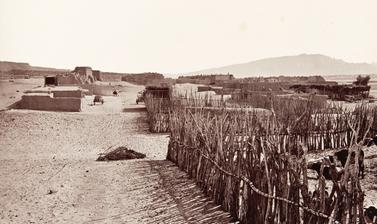 View of Santa Ana Pueblo, with cattle in a corral in the foreground.