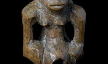 Wooden statue with breasts and a penis.