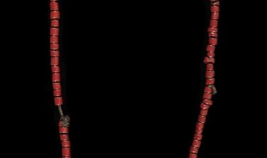 Necklace of red, white and blue beads attached to what looks like a brown leather string with a small amulet of the same material.