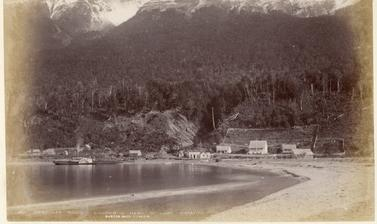 'Humboldt Range – Kinloch – Head of Lake Wakatipu'. View of houses at Kinloch on Lake Wakatipu, with a paddle steamer moored alongside a jetty, and snow-capped mountains of the Humboldt Range in the distance. Photograph by Alfred Burton for the Burton Bro