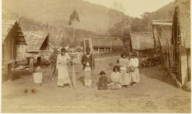 Māori family pictured amidst houses at Pipiriki, a settlement on the east bank of the Whanganui River. Photograph by Alfred Burton for the Burton Brothers studio (Dunedin). Pipiriki, North Island, New Zealand. 11 May 1885. (Copyright Pitt Rivers Museum, U