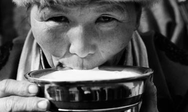 Black and white photo of a person drinking milk from large bowl