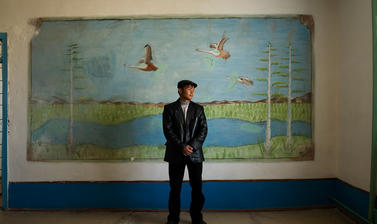 A student posing for a portrait in front of a mural inside his school in Muynaq. This city has been devastated by the shrinking of the Aral Sea. Muynaq, Uzbekistan. Photograph by Carolyn Drake. March 2008.