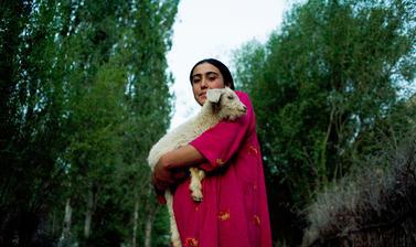 A Pamiri woman carrying home a lamb at dusk. Garm Chashma, Tajikistan. Photograph by Carolyn Drake. July 2008.