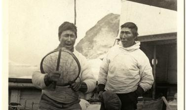 Two Inuit men perform with a drum on the deck of the Quest. Photograph by Henry Iliffe Cozens. Greenland. 1930–1931.