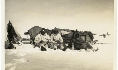 Group portrait of BAARE members resting against a heavily laden sledge, taken during their overland rescue trip to relieve Augustine Courtauld. Photographer unknown. Greenland. 1930–1931.