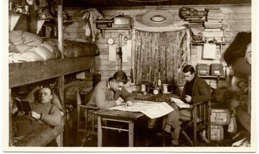 Members of the expedition posed and looking studious in their base hut. Photograph by Henry Iliffe Cozens. Near Angmassalik (now Tasiilaq), Greenland. 1930–1931.