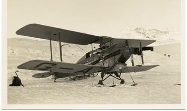 A small De Havilland Moth biplane used in the expedition, shown here with landing gear of skis. Photograph by Hery Iliffe Cozens. Greenland. 1930–1931.
