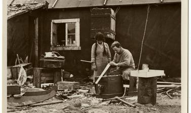 An expedition member working alongside an Inuit woman. Photographer unknown. Greenland. 1930–1931.