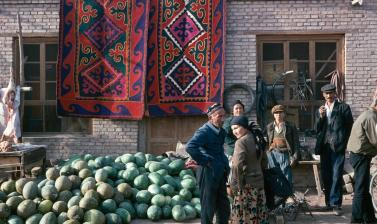 People at a market stall selling watermelons, with two large felt rugs seen hanging on the building behind them. Photograph by Sheila Paine. Kashgar, Xinjiang, China. 1994. (Copyright Pitt Rivers Museum, University of Oxford. Accession Number: 2012.4.354.