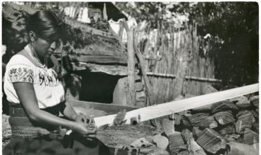 A woman picking up a gauze pattern on a loom. Huauchinanago, Puebla, Mexico. 'The pattern-forming wefts are made individually with the fingers; no material aid is used, so the worker must be able to visualise the design.' Photographed by Elsie Colsell McD