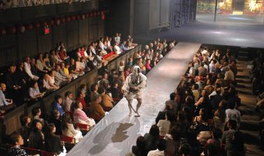 The hanamichi, a raised walkway through the theatre audience (literally 'flower path'), is one of the most characteristic elements of kabuki, used by the actors not only for entrances and exits but also as an integral part of the stage. Here we see Nakamu