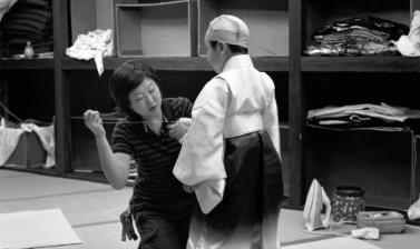 A woman mends the sleeve of a child actor in the costume room of the Kanamaru-za, the oldest wooden theatre in Japan, which was built in 1835 in Kotohira, Kagawa Prefecture. Photograph by Akio Kushida. September 2006. (Copyright Akio Kushida)