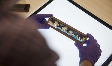 Gloved hands holding a painting of ships at sea, above a lightbox