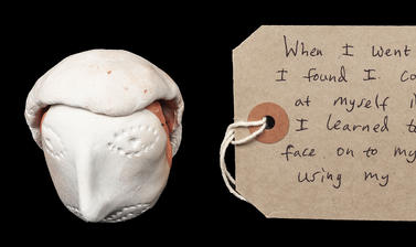 White clay formed into a face with a rectangular brown paper handwritten luggage tag style label