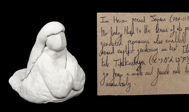 White clay formed into a seated figure with a rectangular brown paper handwritten luggage tag style label