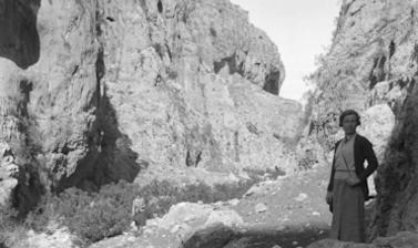 Rocky landscape with a woman standing on right hand side facing the camera.