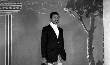 Man with a brief-case standing in front of the photographer's first painted backdrop, created for Touselle when he established Studio Photo Jacques in 1970. Photograph by Jacques Touselle. Mbouda, Cameroon. Early 1970s.