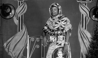 Woman wearing a dress made from fabric printed with Union flags, royal insignia and a circular portrait of Queen Elizabeth II, possibly marking the Queen's Silver Jubilee. Photograph by Jacques Touselle. Mbouda, Cameroon. About 1977.